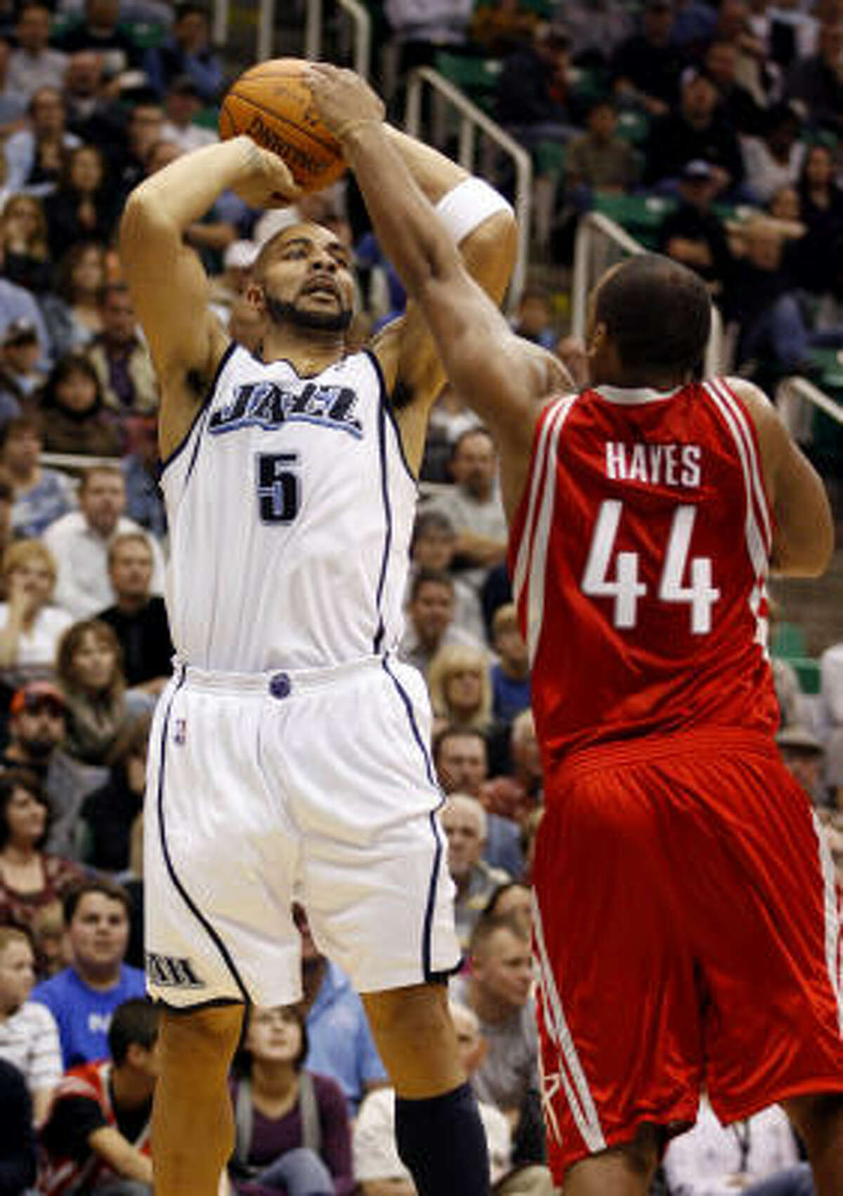 Jazz forward Carlos Boozer puts up a shot over Rockets forward Chuck Hayes. The Rockets held Boozer to 1-for-6 shooting.