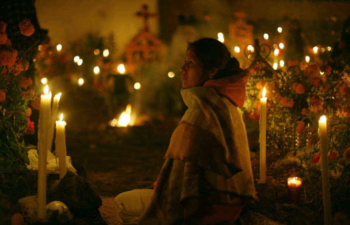A woman sits next to a grave site during Day of the Dead celebrations at the cemetery this morning in Arocutin, Mexico. According to tradition, candles are lit to guide wandering souls back to their families during Day of the Dead.