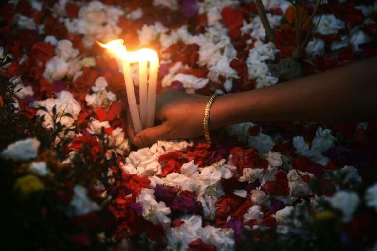 A Christian woman lights candles on the tomb of her relatives on All Souls' Day, in Calcutta, India.