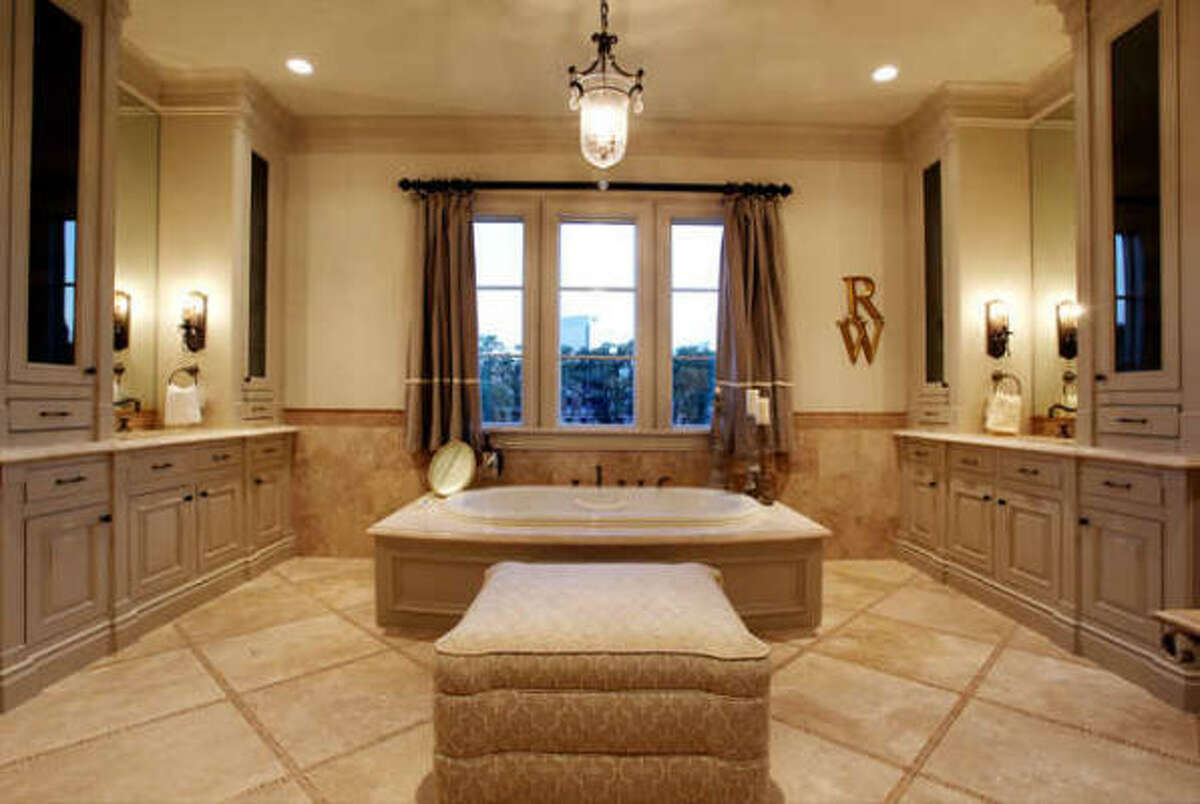 Master bath with travertine mosaic in-laid floor, his & her vanities and dressing areas, hide away plugs in drawers for electronics, air whirlpool tub and zoned body spray shower.