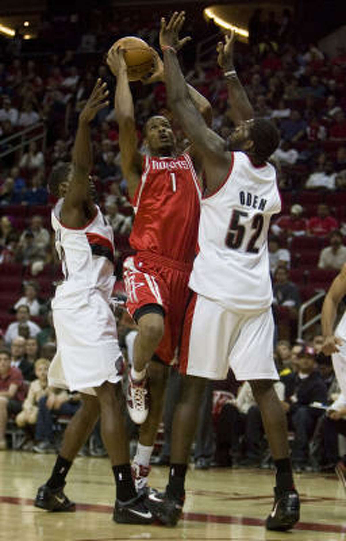 Rockets swingman Trevor Ariza navigates the double-team of Martell Webster, left, and Greg Oden. Ariza led the Rockets with a season-high 33 points on 11-for-17 shooting.