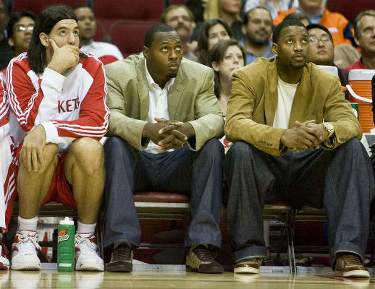 The Houston Rockets Luis Scola, left, sits with the inactive Joey Dorsey, center, and Tracy McGrady. Scola had a rough night from the floor, going 3-for-9, but managed six rebounds in 19 minutes.