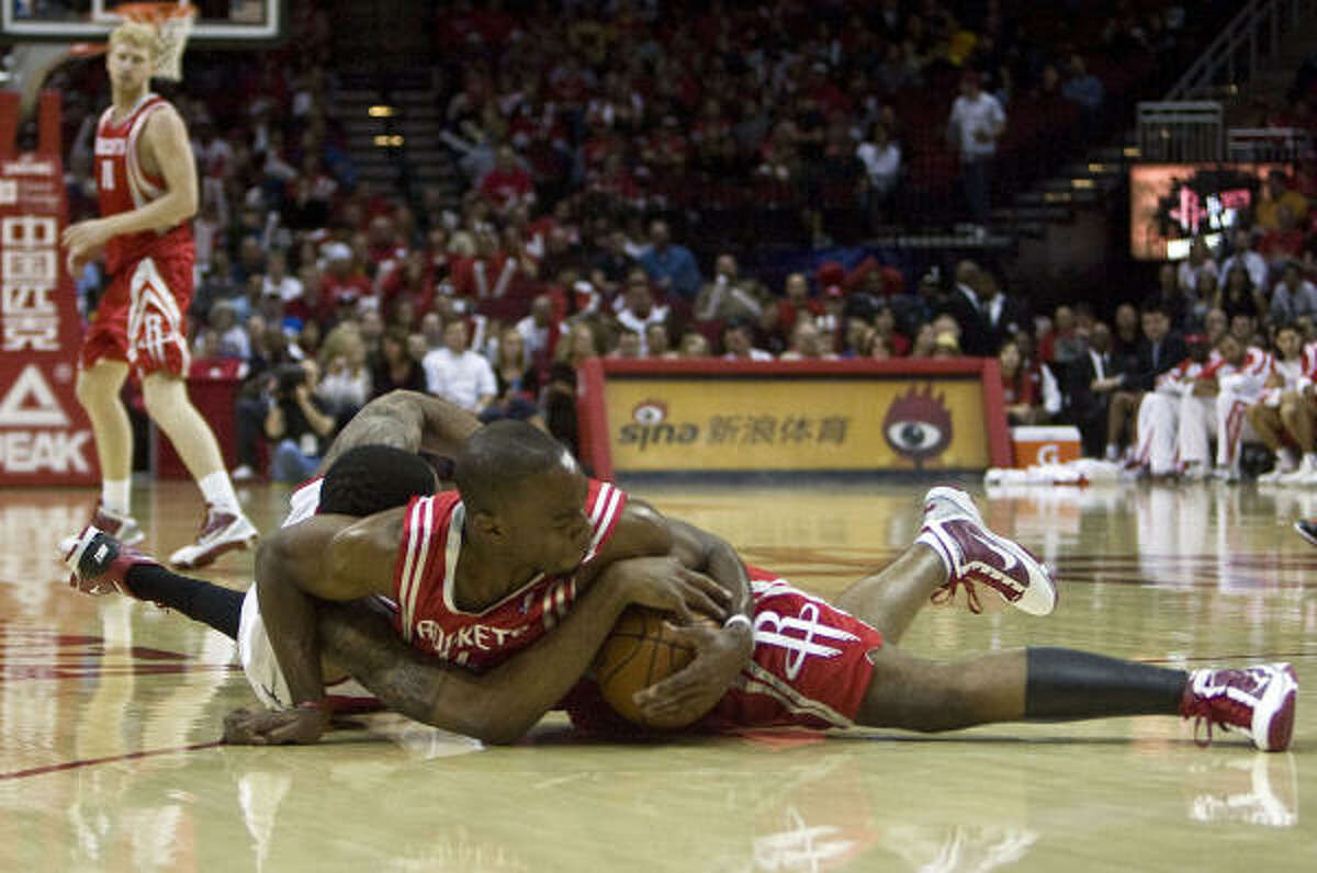 The Rockets's Carl Landry, right and former Texas Longhorn LaMarcus Aldridge of the Blazers wrestle for the ball.
