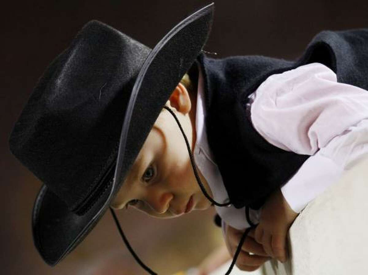 A young Oklahoma State fan looks down at the players on the field at Boone Pickens Stadium in Stillwater Okla. The No. 3 Longhorns are in town to face the No. 13 Cowboys.