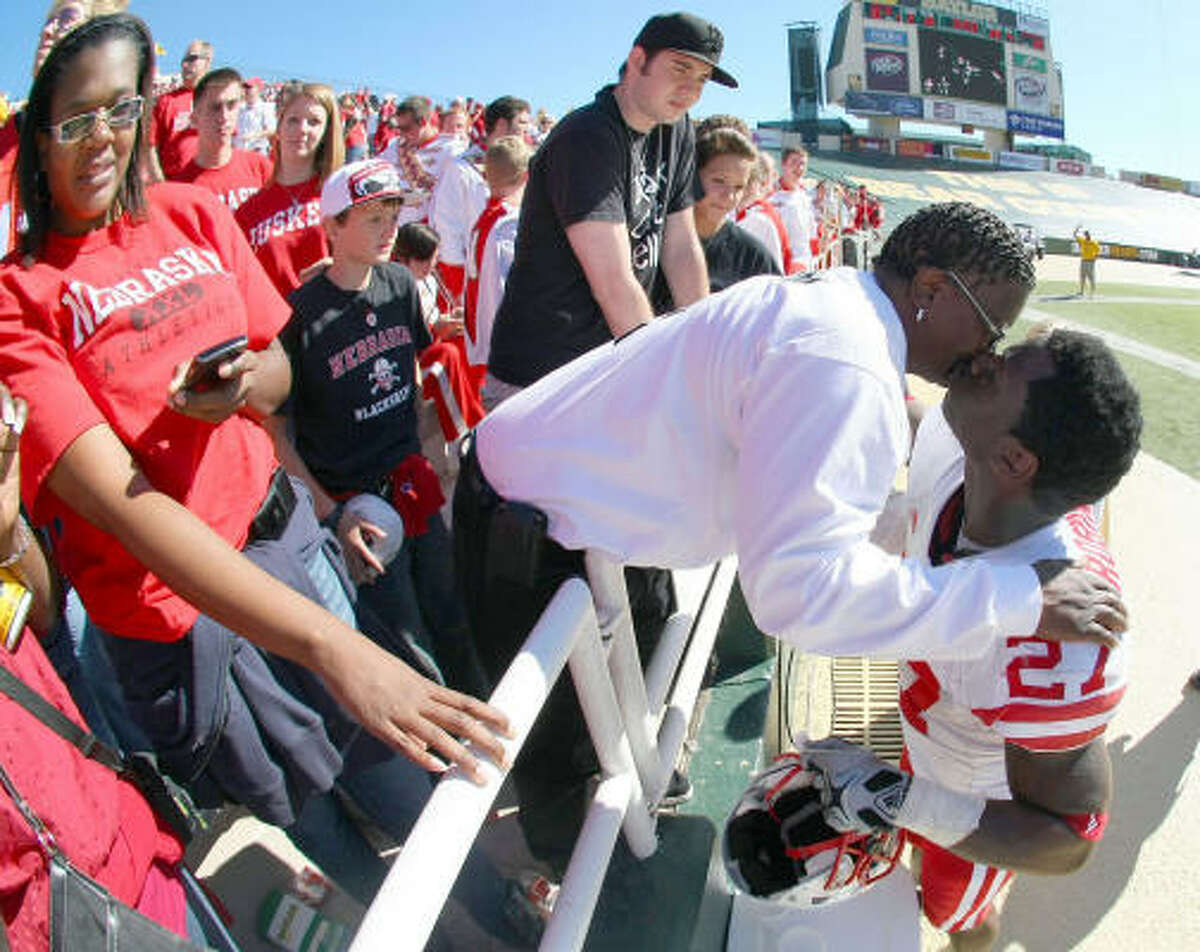 Nebraska running back Dontrayevous Robinson kisses his mother, Linda Robinson, after the Cornhuskers' victory.