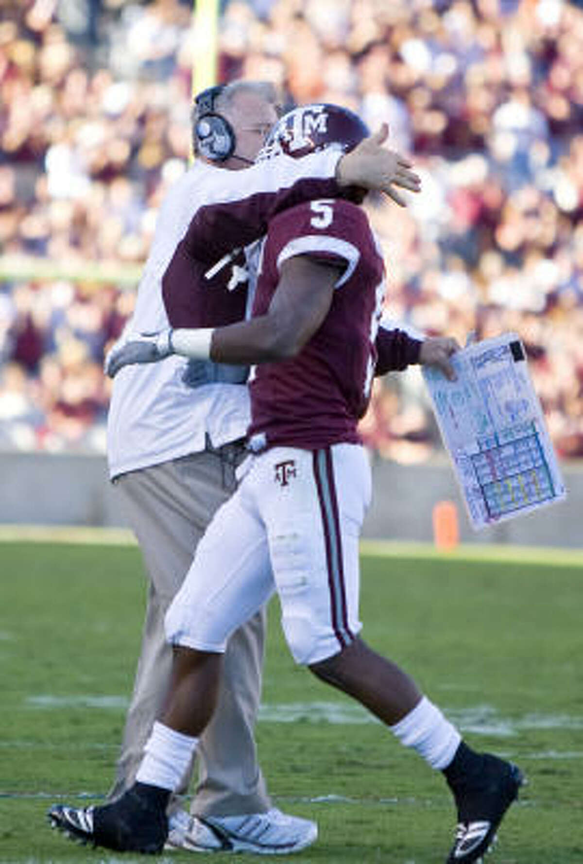 A&M's Howard Morrow gets a hug from coach Mike Sherman on the sidelines after his touchdown during Saturday afternoon's game in College Station.