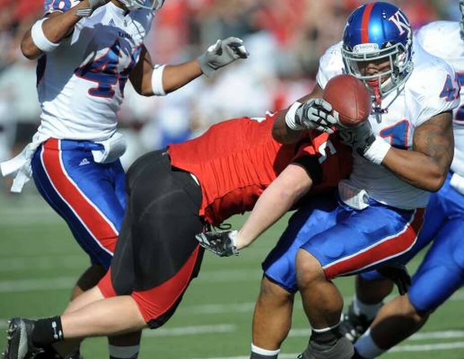 Kansas' Arist Wright, right, fumbles as he is hit by Texas Tech's Ryan Hale near the end of the first half of Saturday afternoon's game in Lubbock. Photo: John A. Bowersmith, Associated Press