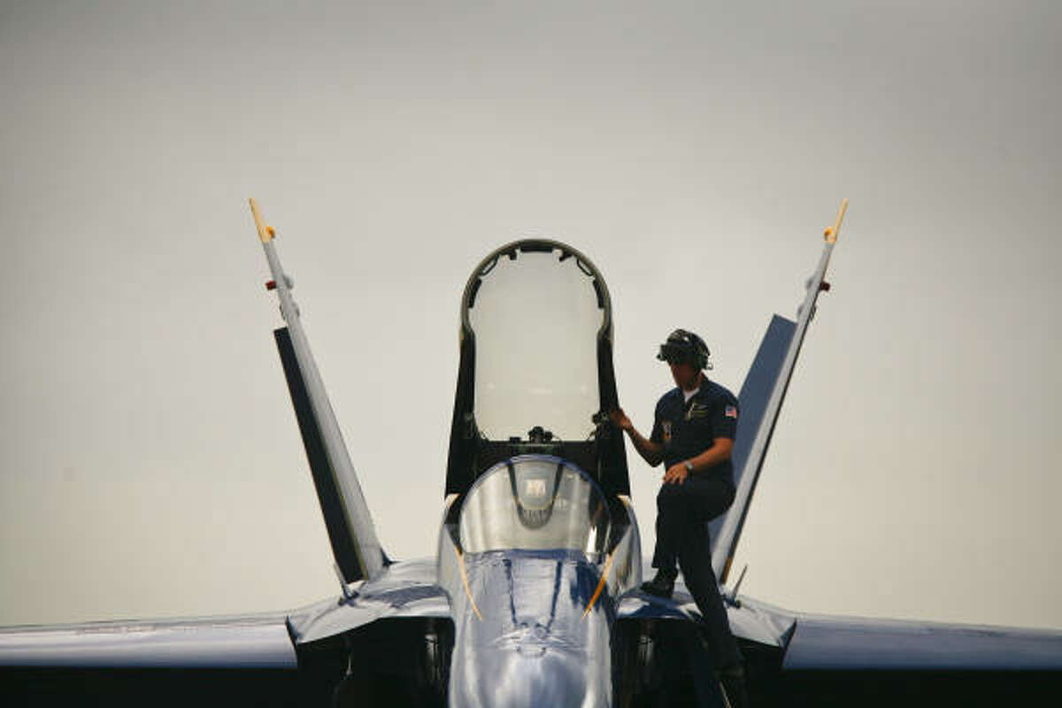 A member of the Blue Angels' maintenance crew checks out one of the supersonic jets after arrival.