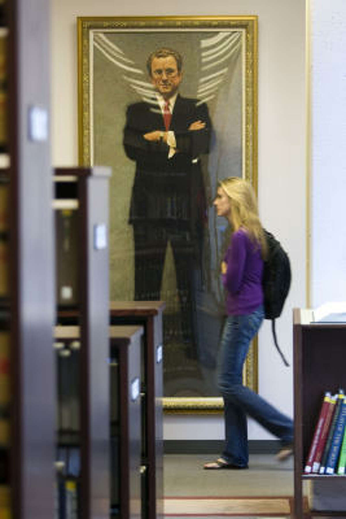 A student walks past a painting of prominent Houston lawyer John O'Quinn in the law library at UH.