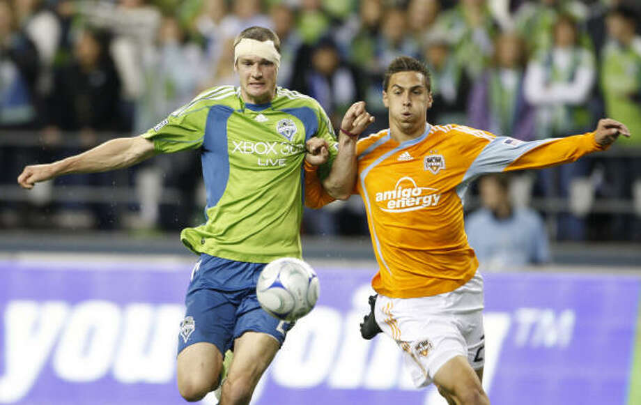 Seattle's Nate Jaqua, a former Dynamo, battles for the ball with Dynamo defender Geoff Cameron, right, in the second half. The match ended in a scoreless tie. Photo: Kevin P. Casey, AP