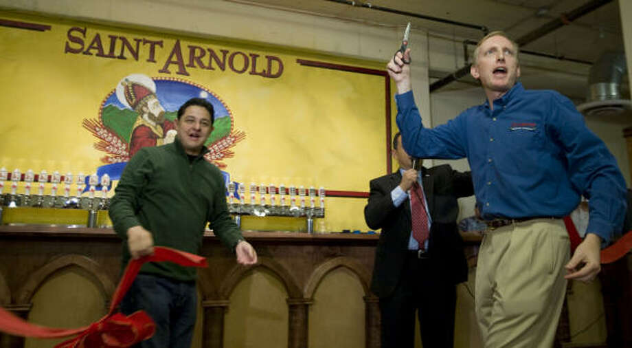 St. Arnold Brewing Co. founder Brock Wagner, with city councilman James Rodriguez, officially opens the bar after cutting a ribbon during the grand opening party for the St. Arnold Brewing Company's new facility in Houston. Saint Arnold is the only craft brewer in Houston and the oldest craft brewer in Texas. The new brewery location, in the 2000 block of Lyons, is a significant move for the 15-year-old company because it will increase production capacity four-fold. Photo: Brett Coomer, Chronicle