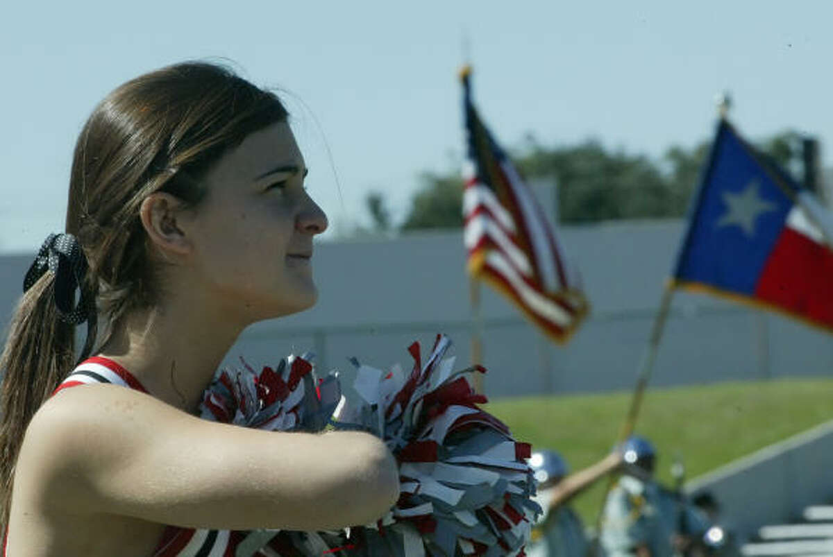 A Waltrip cheerleader listens as the Stars and Stripes drifts across the field before the start of the game.