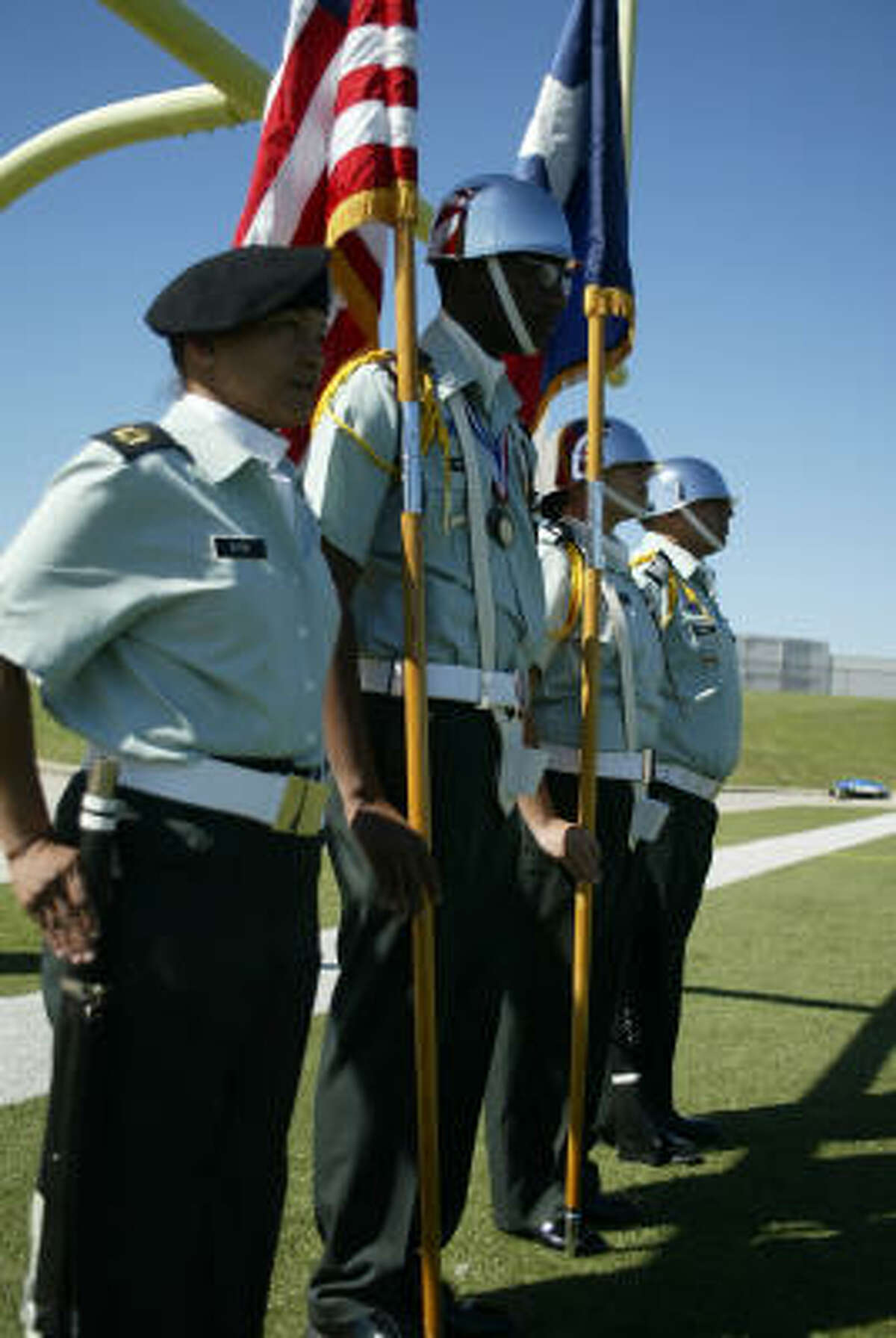 The ROTC color guard stands at attention as they await their cue to march to center field.
