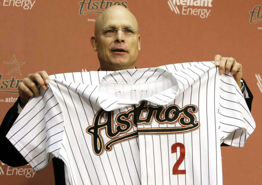Brad Mills holds up his new jersey during a news conference at Minute Maid Park after he was named manager of the Astros. Photo: Brett Coomer, Chronicle