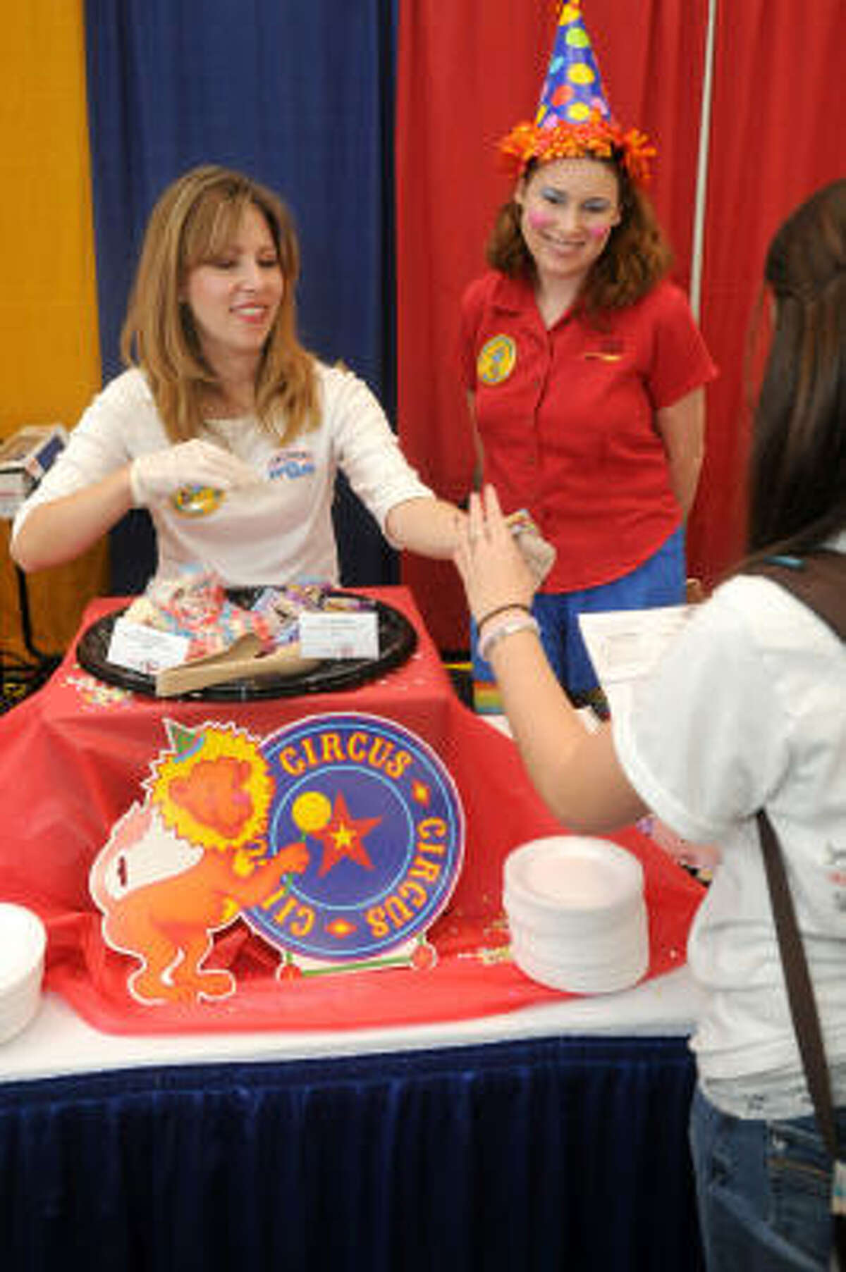 Food Co-op Expo: Valerie Karchmer, left, of Dallas, at her J.M. Smuckers booth, with clown Anna Rosa of Houston, shares a sample with Kristin Smith, 14, a freshman at Atascocita High School.