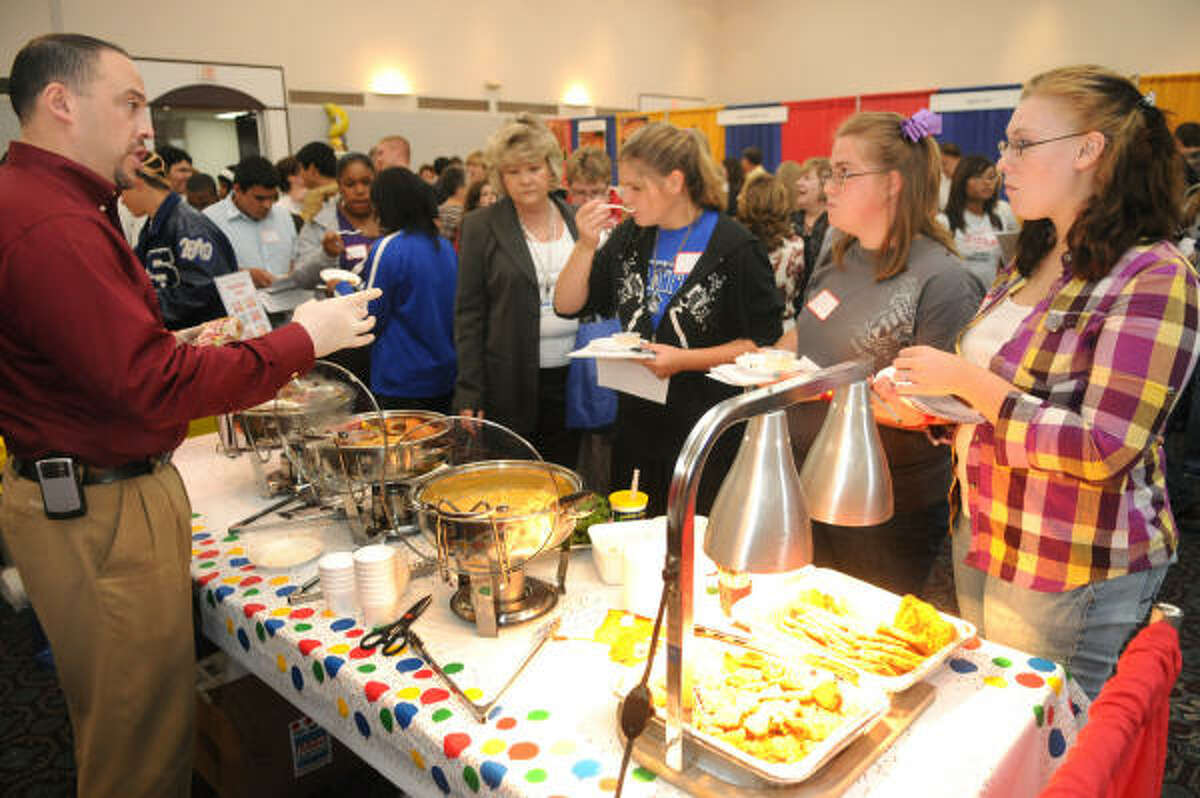 From right, Kayla Cooper, 18, Dustie Grace, 17, and Ariel Young, 18, all seniors at Shepherd High School, try the food samples offered by Steve Turner, left, of St. Paul, Minn, who is the Texas market representative for Pierce Foods.