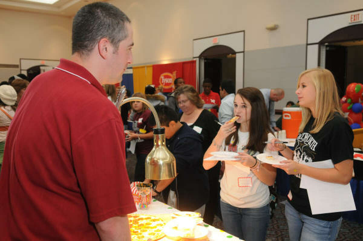 Christina Smith, 16, right, a junior at Atascocita High School, and Kristin Smith, 14, a freshman at AHS, sample a pizza from UNO Foods and Jeff Keating, left. The expo offered 400 students and staff from 45 school districts the opportunity to sample food that could appear on school lunch menus.