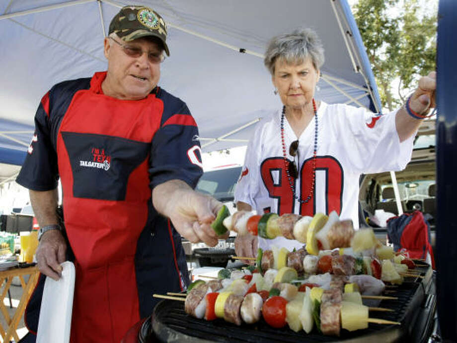 Texans fans E.L. Toppel, left, of Matagorda, and Sally Rankin, of La Porte, grill kabobs as they tailgate before the game against the San Francisco 49ers at Reliant Stadium. Photo: Brett Coomer, Chronicle