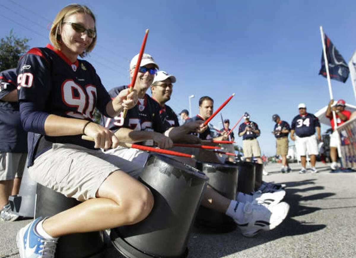 Members of the Texans' Bull Pen pep band use buckets as drums as they play for tailgaters before the game at Reliant Stadium.