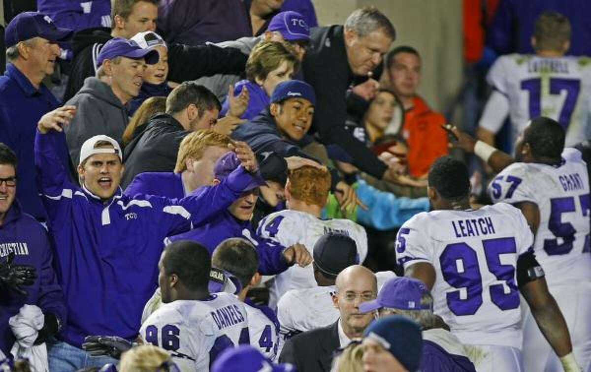 Fans and players celebrate after TCU's victory against BYU in Provo, Utah.