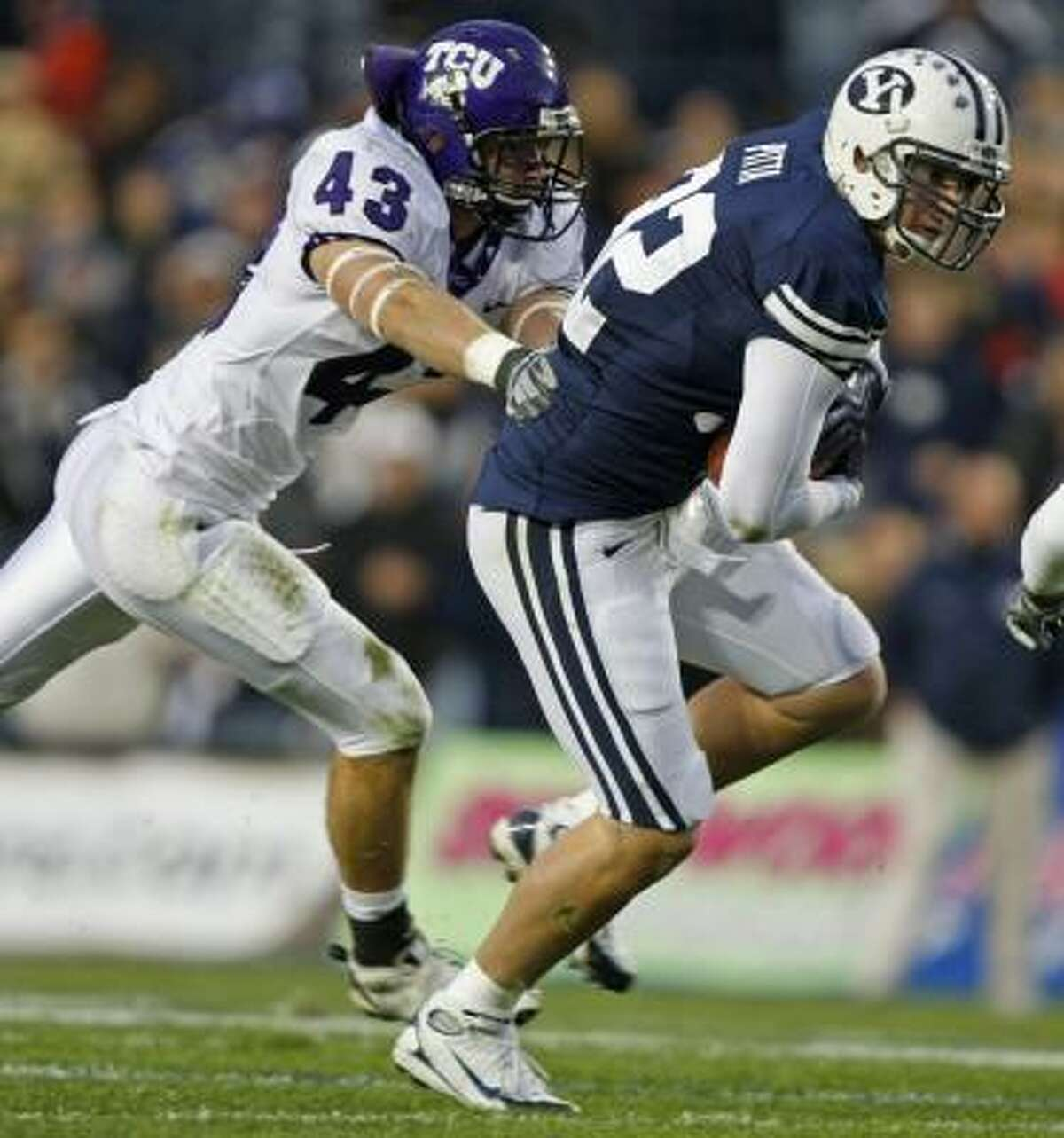 BYU's Dennis Pitta, right, catches a pass against TCU's Tank Carder during the first half.