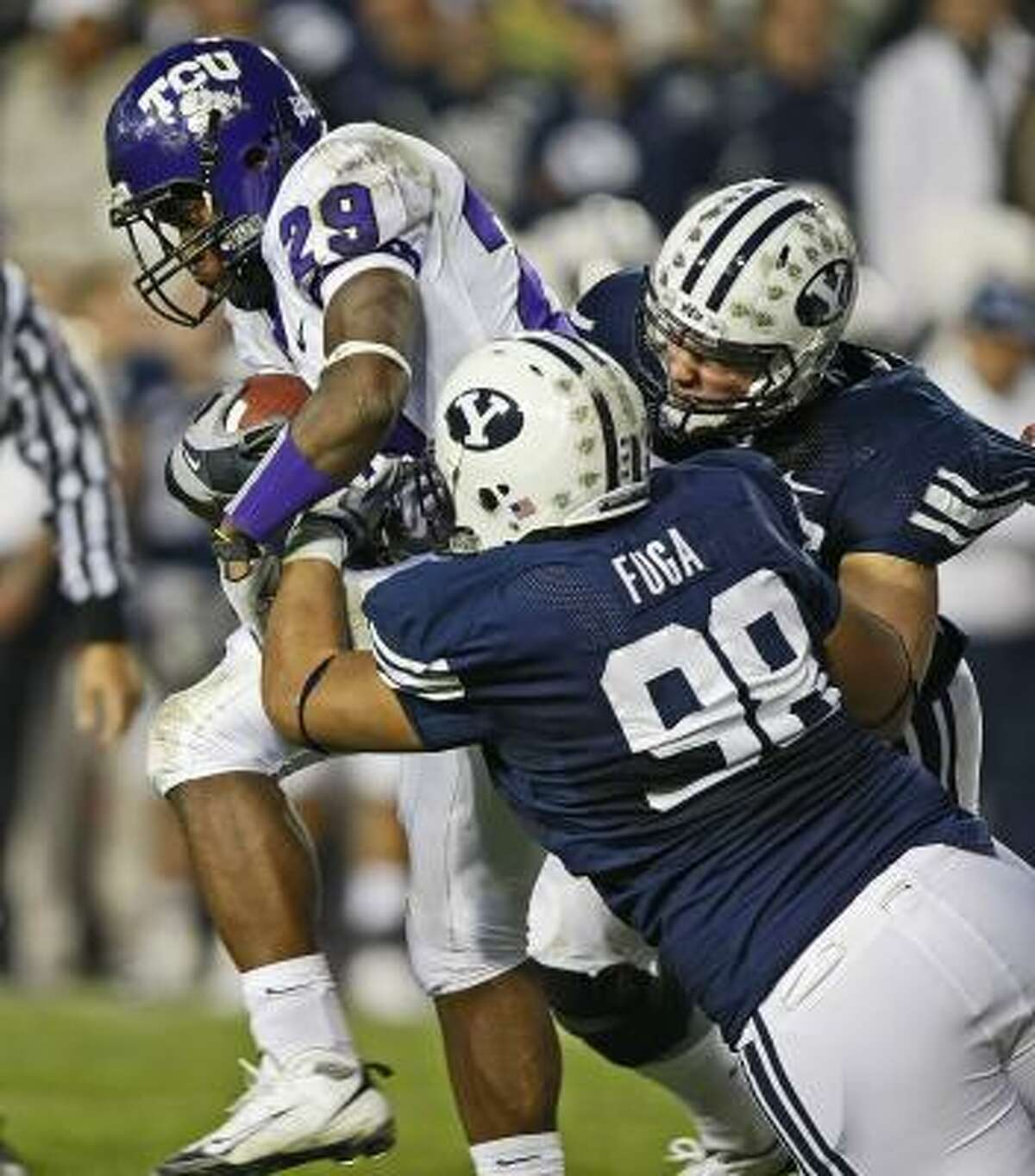 TCU's Matthew Tucker (29) is tackled by BYU's Romney Fuga (98) and Matt Bauman during the first half.