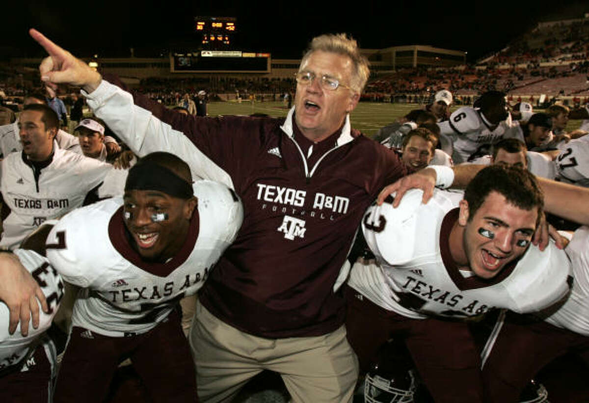 Texas A&M coach Mike Sherman celebrates with players Uzoma Nwachukwu, left, and Aaron Arterburn after Saturday's victory against Texas Tech in Lubbock.
