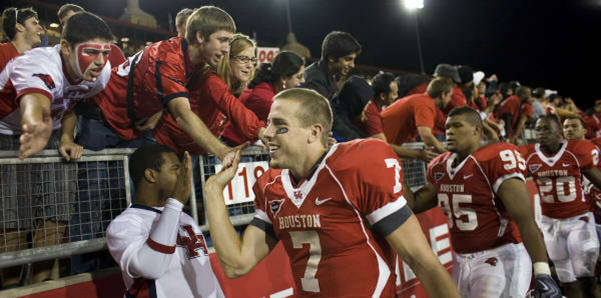 Houston quarterback Case Keenum (7) gives the fans high-fives after beating SMU on Saturday night at Robertson Stadium.