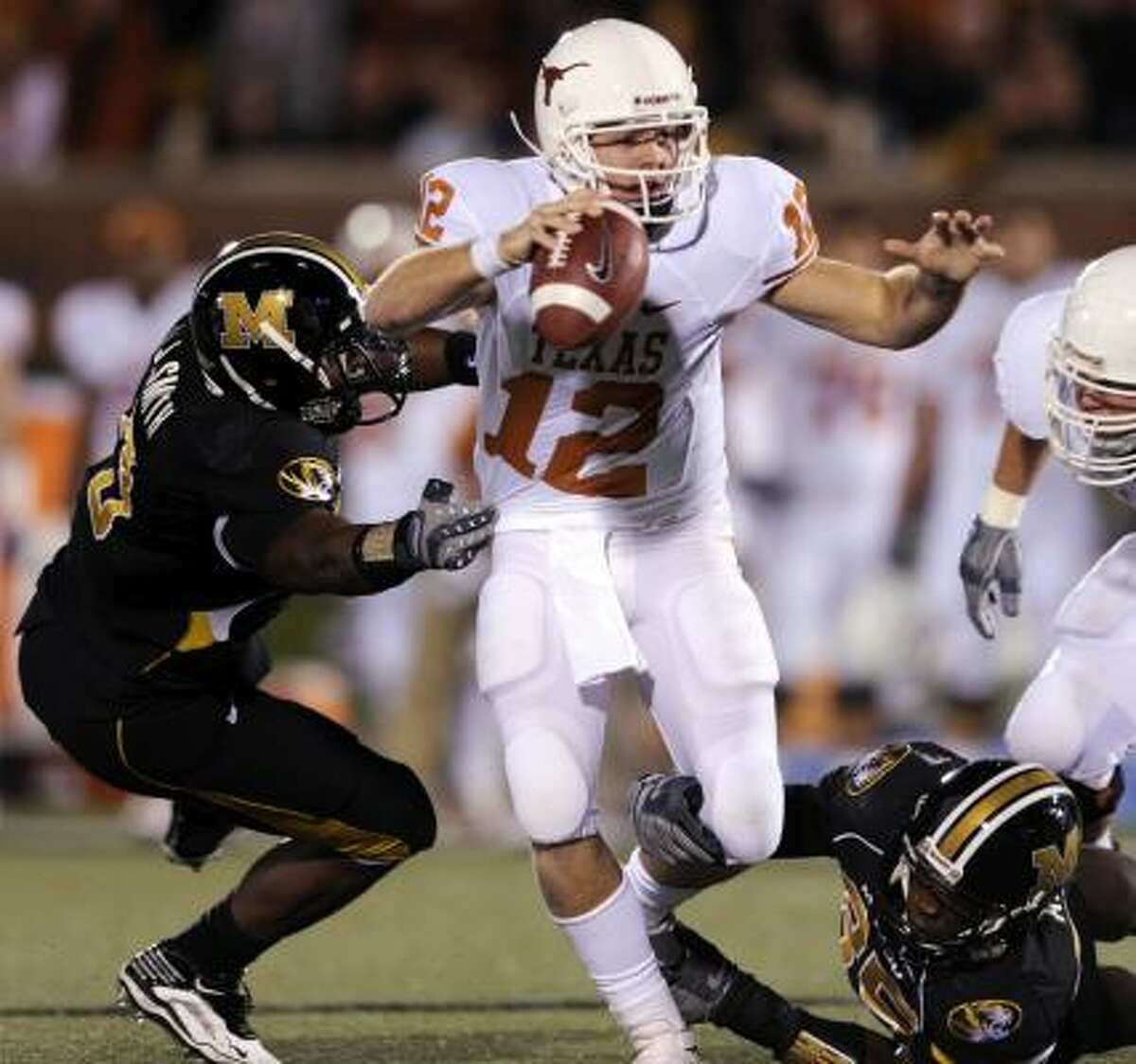 Texas quarterback Colt McCoy, center, tries to avoid Missouri defenders Jacquies Smith, left, and Aldon Smith, right, during the second quarter.