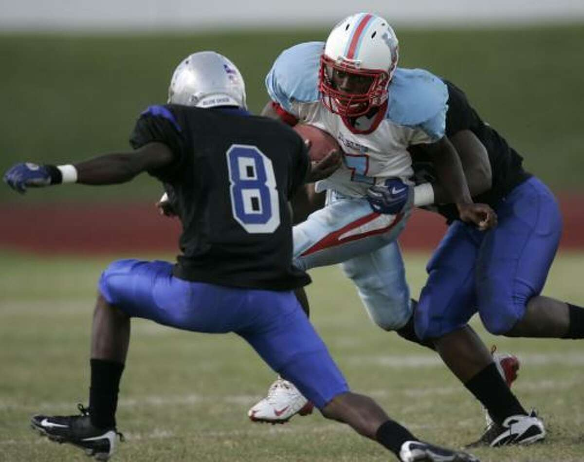Madison's Terrence Smith (7) tries to escape Chavez's James Johnson (right) and Christian Gamboa (8) in the first quarter.