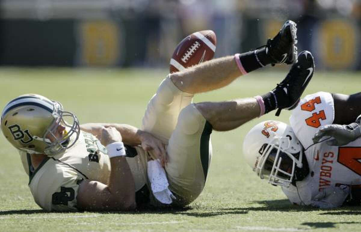 Baylor quarterback Blake Szymanski is sacked by Oklahoma State linebacker Donald Booker during the second half.