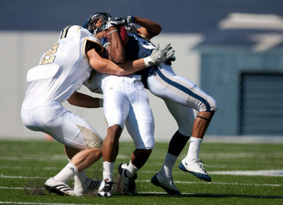 Rice's Michael Poynter gets collared by Central Florida defenders Michael Greco, left, and Josh Robinson. Photo: Nick De La Torre, Chronicle