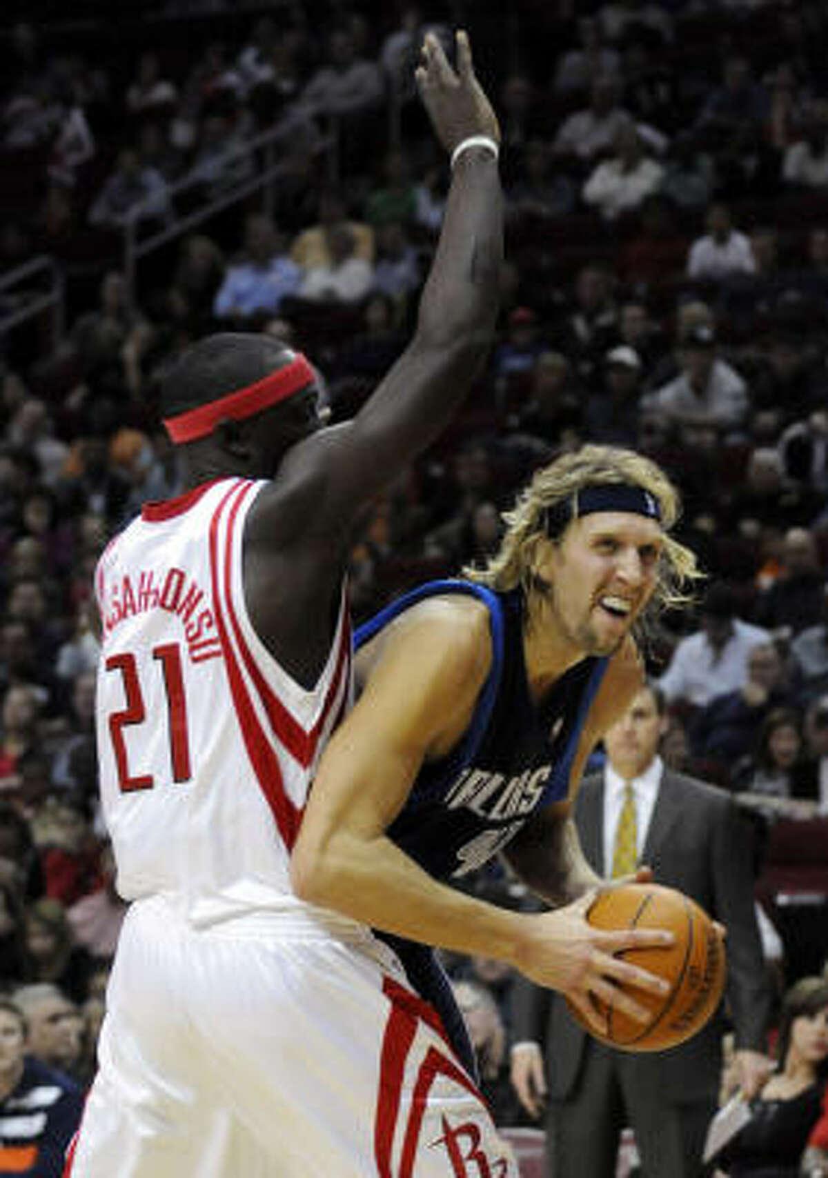 Mavericks forward Dirk Nowitzki, right, tries to get around Houston's Pops Mensah-Bonsu in the first half.