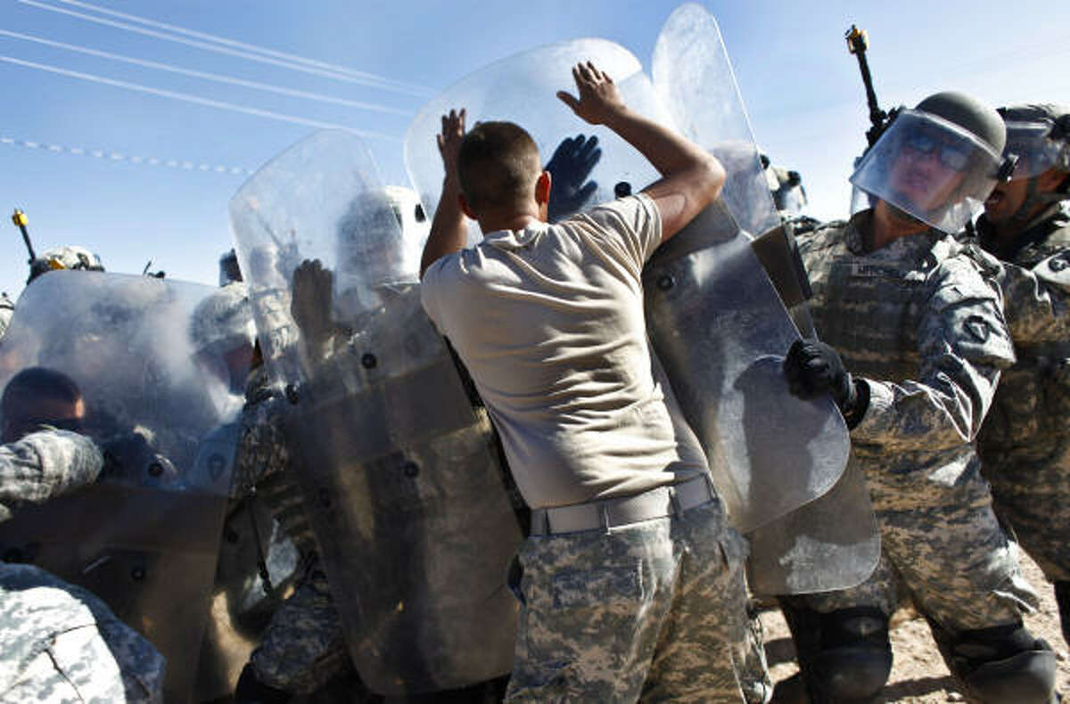 Spc. Jacob Mitchell, of Santa Fe, blocks a fellow soldier playing a rioter during Riot Control training at Camp McGregor, NM. Mitchell is a member of Delta Company, 3rd Battalion, 141st Infantry Regiment of the 72nd Infantry Brigade Combat Team, a Texas National Guard unit headed to Iraq at the end of this year.