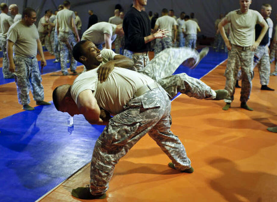 Spc. Adam Ross, 36, of Houston, flips Pfc. Lawrence Norwood, 19, of Texarkana during the Unarmed Self Defense Training. The soldiers are members of Delta Company, 3rd Battalion, 141st Infantry Regiment, 72nd Infantry Brigade Combat Team, a Houston-based Texas National Guard unit headed to Iraq at the end of this year. Photo: Mayra Beltran, Chronicle
