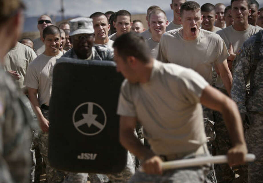 Members of 72nd Infantry Brigade Combat Team cheer for an instructor who was sprayed with Oleresin Capsicum (OC) Spray, or pepper spray. The soldiers are sprayed so they will know what it feels like and how to fight through the pain. The soldiers are members of Delta Company, 3rd Battalion, 141st Infantry Regiment, 72nd Infantry Brigade Combat Team, a Houston-based Texas National Guard unit headed to Iraq at the end of this year. Photo: Mayra Beltran, Chronicle
