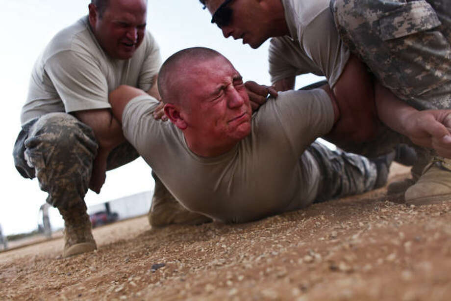 Pfc. Bryan Horner, 20, of Sugar Land, is taken down by fellow soldiers practicing non-leathal force while experiencing the effects of Oleresin Capsicum (OC) Spray (or pepper spray). The training is designed to let soldiers know what it feels like to be sprayed  and how to fight through the pain. Photo: Mayra Beltran, Chronicle