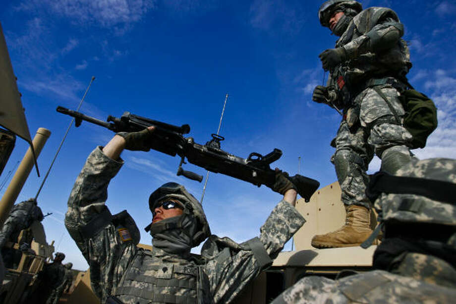 Spc. Ford and helps dismount weapons after the Convoy Live Ops Lane Convoy Live Ops Lane, where soldiers practice scanning the road for bombs and shoot targets with live fire. Photo: Mayra Beltran, Chronicle