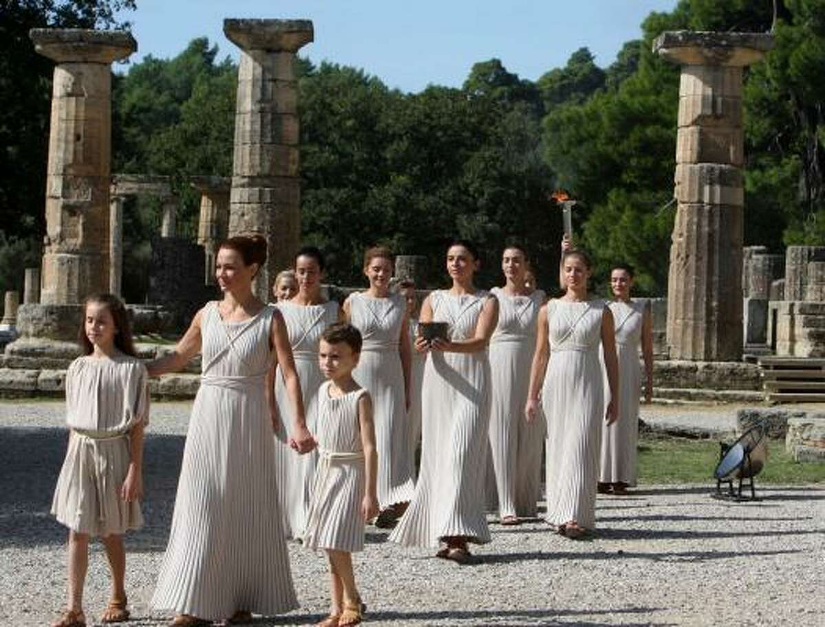 Performers dressed as priestesses walk with the Olympic flame during the lighting ceremony for the Vancouver 2010 Winter Games at the temple of Hera in Ancient Olympia, western Greece, on Thursday.