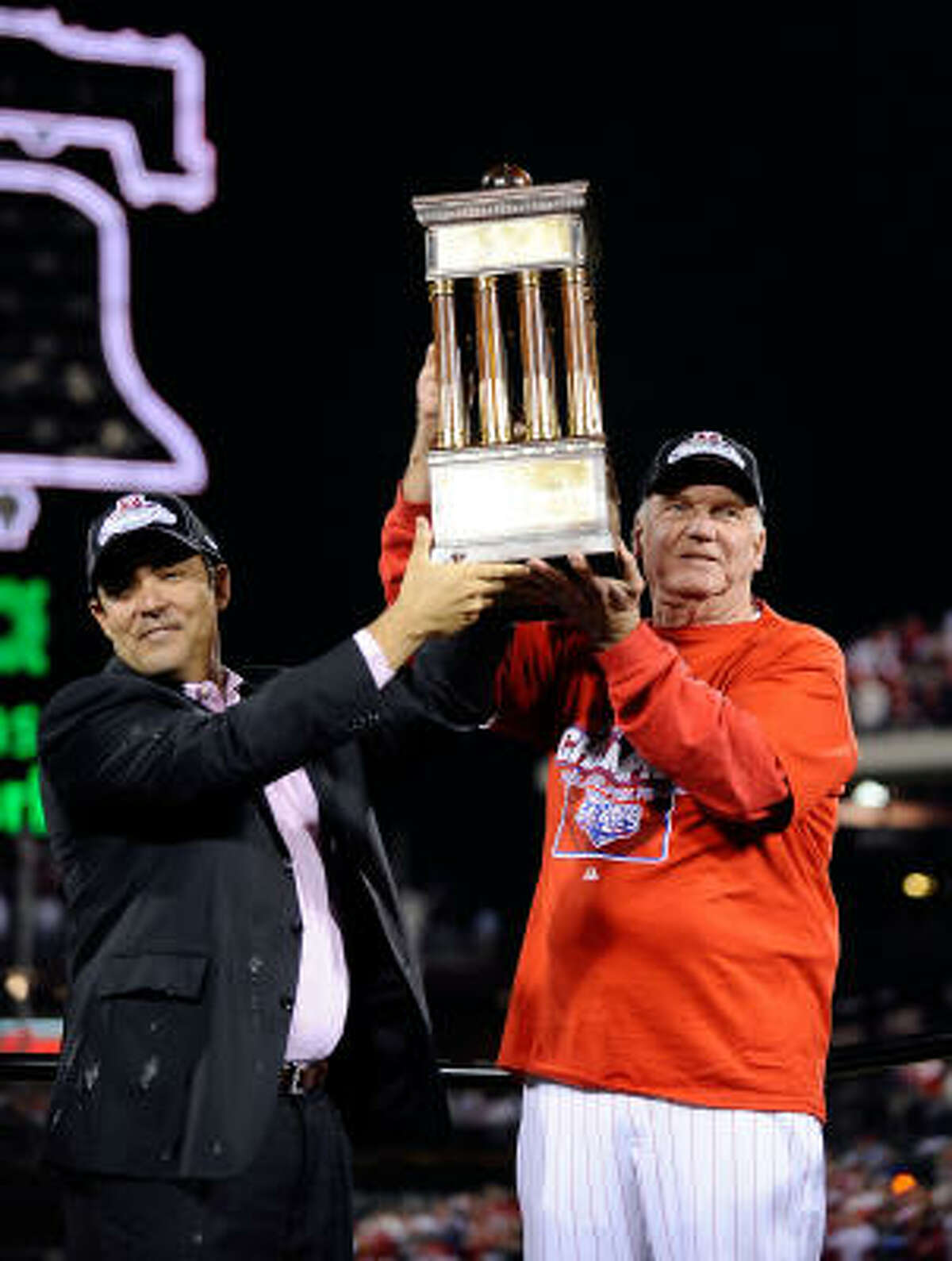 Phillies manager Charlie Manuel of the holds the National League trophy with GM Ruben Amaro Jr. as they celebrate defeating the Dodgers 10-4 to advance to the World Series.