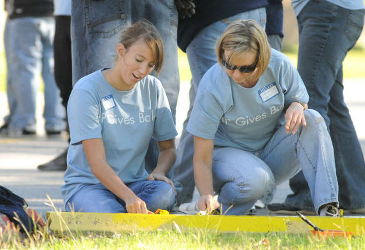 NIMITZ CLEANUP: Nicole Kubera, 15, a freshman at Cy-Fair High School, and her mom, Lorena, an employee of Hewlett-Packard, paint parking blocks in the front parking lot of Nimitz High School. As part of the project hosted by the HandsOn Network, HP, students and community volunteers joined together to spruce up the NHS grounds, both inside and out.