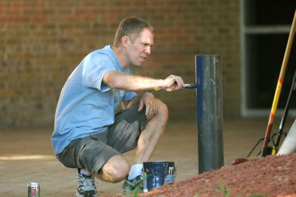 Gilbert Herve, an employee of Hewlett-Packard, paints a parking block near the front entrance of Nimitz High School.