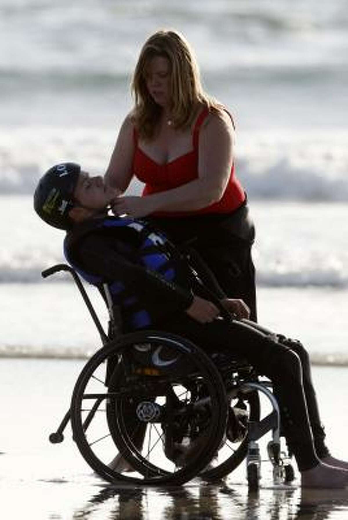 Ivison has his helmet tightened by his mother, Jennifer Kayler, as he prepares for a surfing session.