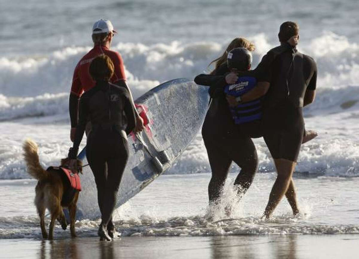 Patrick is carried into the ocean by his mother and friends. His surfing partner, Ricochet, is a SURFice dog that works with special needs surfers and helps raise funds for charitable causes.