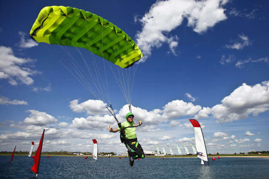 David Billings glides over the water during the swoop competition portion of the US Parachute Association National Skydiving Championships at Skydive Spaceland Tuesday in Rosharon. Photo: Michael Paulsen, Chronicle