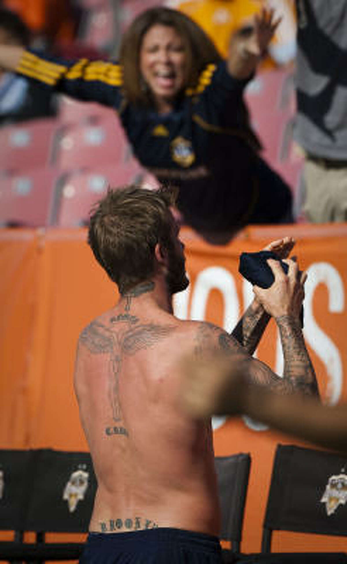 David Beckham of the Los Angeles Galaxy tosses his jersey into the stands following the game.