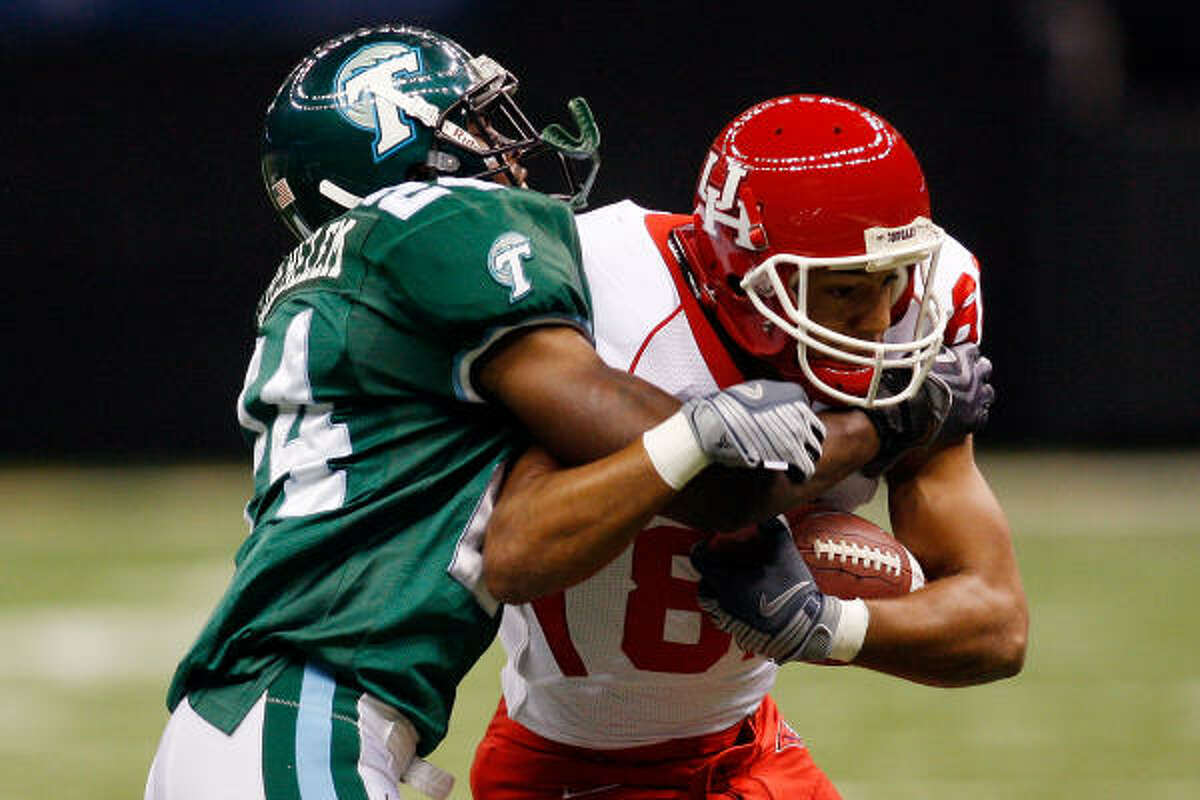 UH's Chaz Rodriguez, right, battles for extra yardage against Tulane's Chinonso Echebelem on Saturday at the Louisiana Superdome.