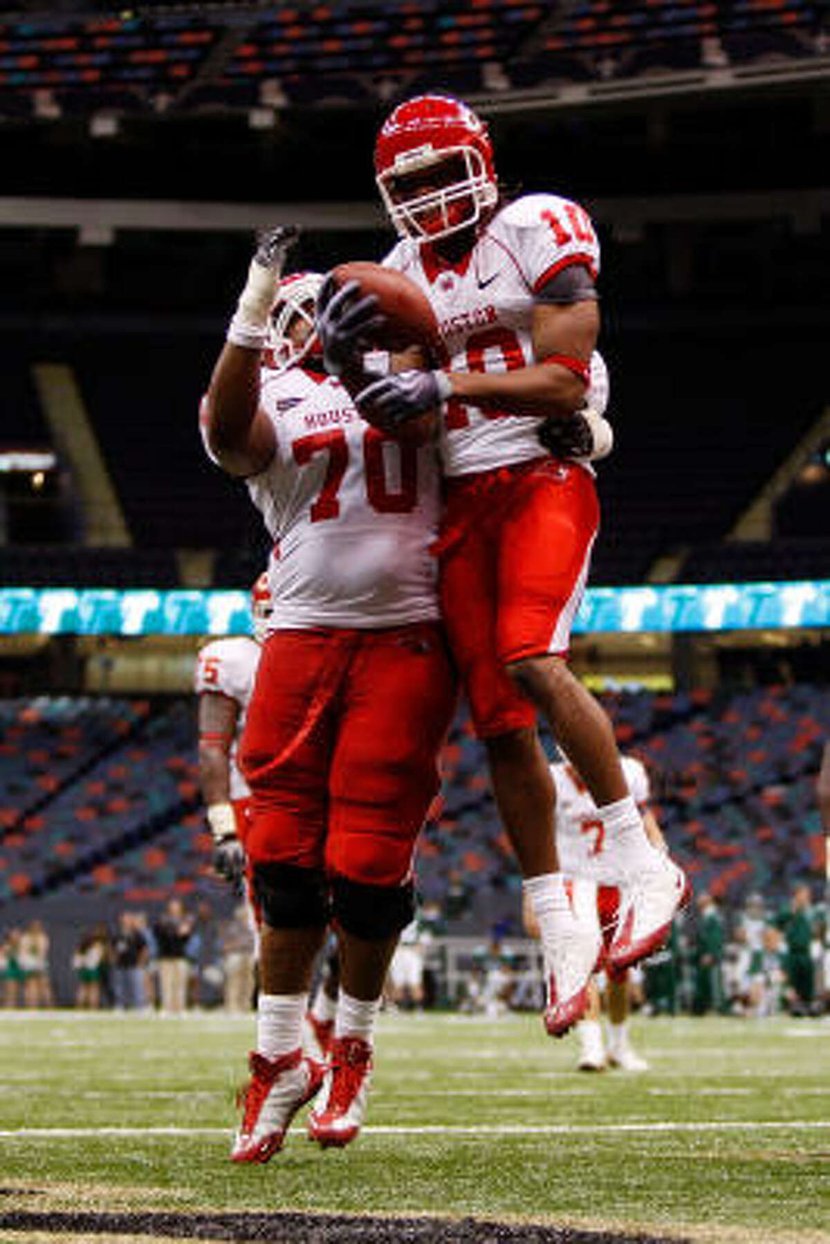 The University of Houston's L.J. Castile, right, celebrates with Chris Thompson after scoring a touchdown against Tulane during the Cougars' victory Saturday at the Louisiana Superdome in New Orleans.