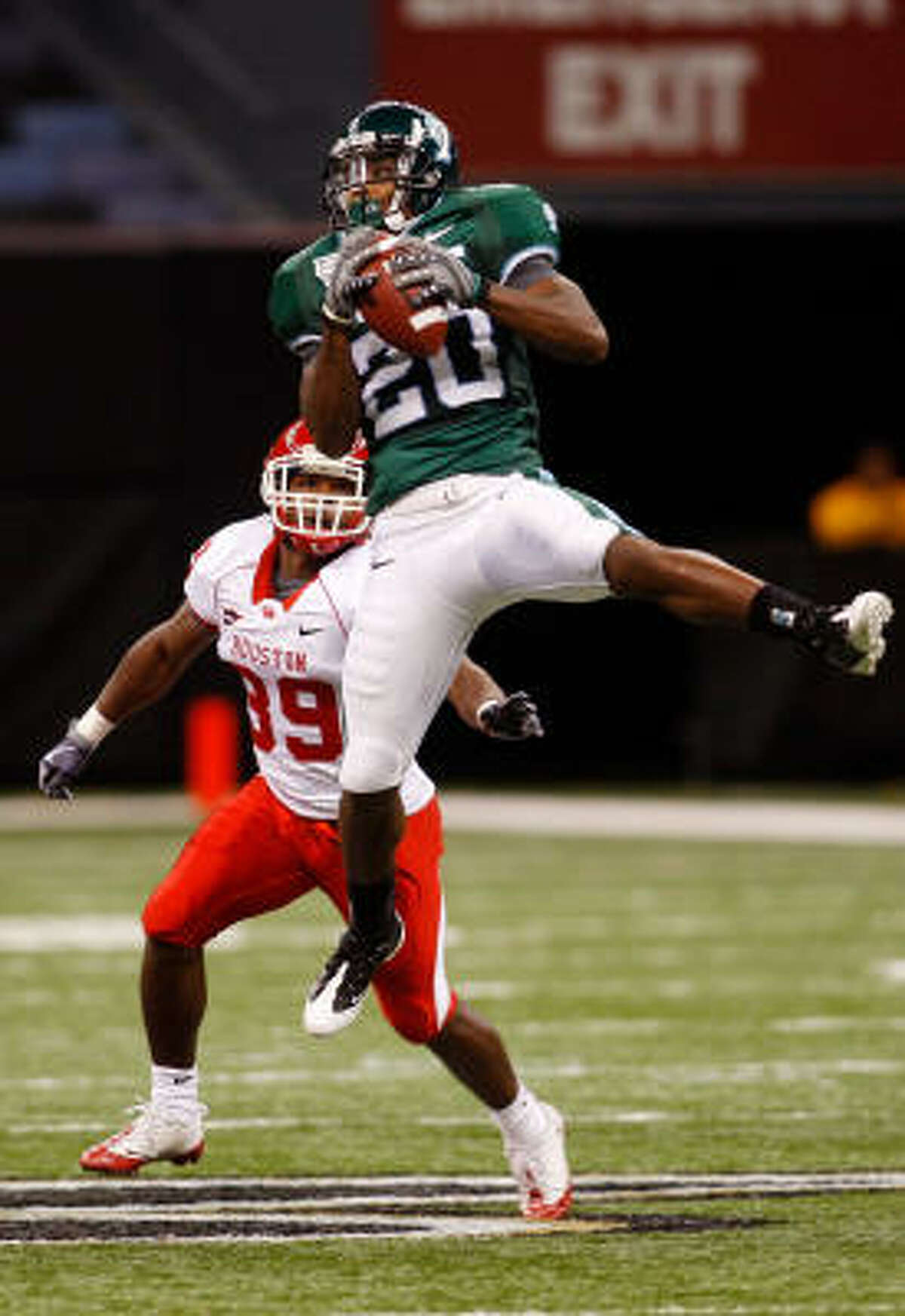 Tulane's Jeremy Williams catches a pass in front of UH's Roisean Haynes.