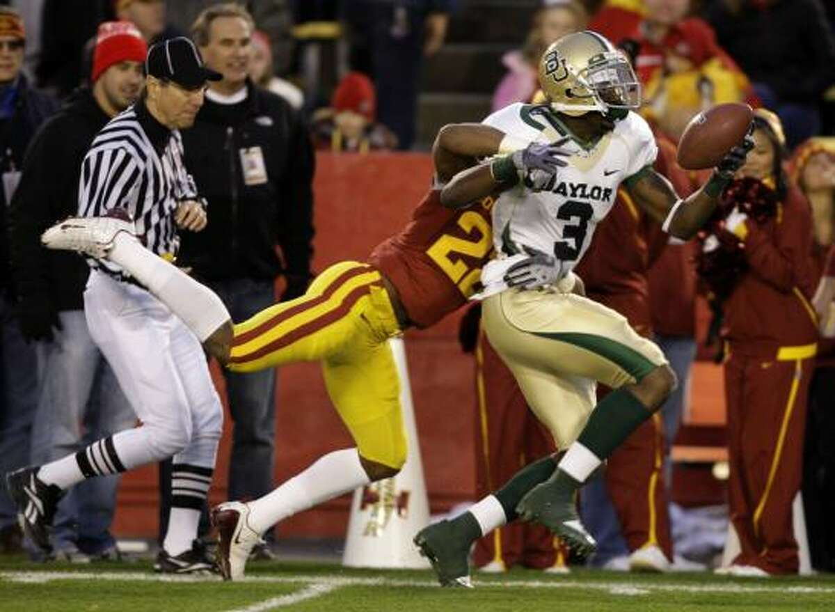 Baylor's Ernest Smith tries to escape the grasp of Iowa State's Ter'ran Benton after making a reception.